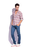 Man with hands in pockets looks away. Young casual man posing with hands in pockets and looking away from the camera Stock Photos