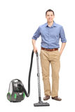 Young casual man posing with a vacuum cleaner Royalty Free Stock Photography