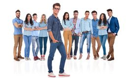 Young casual man presenting his team standing behind. Young casual men with glasses and hand in pocket presenting his team standing behind on white background royalty free stock photography