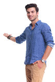Young casual man presenting or inviting Royalty Free Stock Image