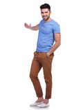 Young casual man presenting something. Full body picture of a young casual man presenting something onwhite background Stock Photos