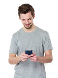 Young casual man reading something on his phone and smiling Stock Photos