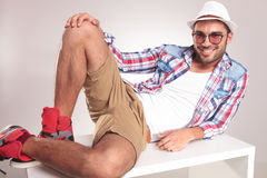Young casual man resting on a white table Royalty Free Stock Image