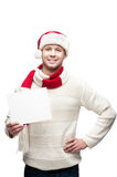 Young casual man in santa hat hoding christmas Royalty Free Stock Photos