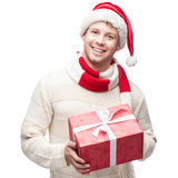 Young casual man in santa hat hoding christmas gift Stock Photography