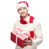 Young casual man in santa hat hoding christmas gift Stock Image