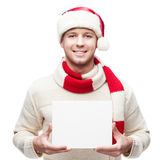 Young casual man in santa hat hoding sign Royalty Free Stock Photography