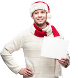 Young casual man in santa hat hoding sign Royalty Free Stock Photos