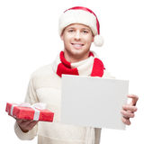 Young casual man in santa hat hoding sign and christmas gift Royalty Free Stock Photo