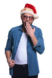 Young casual man in santa hat is yawning Royalty Free Stock Photo