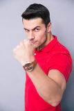 Young casual man showing fist. Over gray background and looking at camera Stock Photo