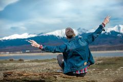 Young casual man sits on  wood log and celebrates freedom. Young casual man sits on a wood log and celebrates freedom with hands in the air while admiring the stock photography