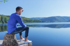 Man sits by the lake & looks away Royalty Free Stock Photo