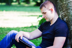 Young casual man sitting on the ground and leaning to a tree Stock Photography