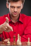 Young casual man sitting over chess. Royalty Free Stock Images