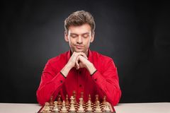 Young casual man sitting over chess. Stock Images
