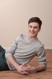 Young casual man sitting and smiling to the camera. Royalty Free Stock Photo