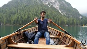 Young man rowing in boat on mountain lake. Young casual man sitting in wooden boat and rowing while looking away on background of lake and mountains. Braies lake stock video footage