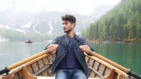 Young man rowing in boat on mountain lake stock video