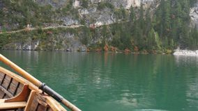 Young man rowing in boat on mountain lake stock video footage