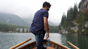 Young man rowing in boat on mountain lake. Young casual man sitting in wooden boat and then standing up while looking away on background of lake and mountains stock footage