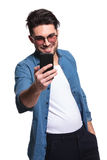 Young casual man smiling while texting Royalty Free Stock Photos