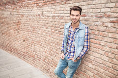Young casual man smilling, leaning on a brick wall Stock Image