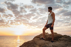 Young casual man standing on the mountain rock Stock Photos
