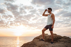 Young casual man standing on the mountain rock Royalty Free Stock Images