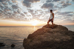 Young casual man standing on the mountain rock Stock Image