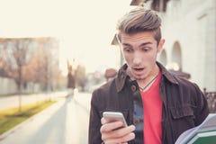 Shocked man watching phone on street royalty free stock photo