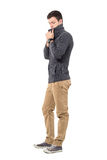 Young casual man in sweater adjusting collar looking down. Side view. Full body length portrait isolated over white background Royalty Free Stock Photography