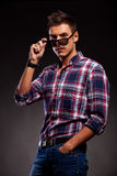 Young casual man taking down his sunglasses. Serious young casual man taking down his sunglasses. Young casual man looking at the camera over his sunglasses . On Stock Images