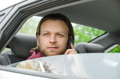 Young casual man talking on the mobile phone in car. Young casual man talking in car royalty free stock photo