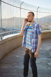 Young casual man talking by mobile phone outdoor Royalty Free Stock Photography