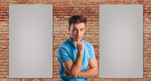 Young casual man thinking near two blank billboards Royalty Free Stock Photography
