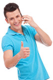 Young casual man thumb up on phone Stock Image