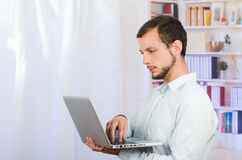 Young casual man using laptop Royalty Free Stock Photo