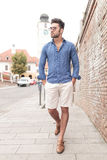 Young casual man walking and looks to side Stock Photos