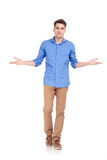 Young casual man walking while welcoming you. Royalty Free Stock Photo