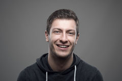 Young casual man wearing sporty hoodie smiling and looking at camera Stock Image