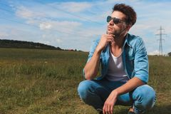 Young casual man crouching in a field and thinking. Young casual man wearing sunglasses and denim shirt crouching in a field and thinking while looking up to stock photography