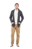 Young casual man wearing unzipped jumper laughing with hands in pockets. Royalty Free Stock Photos