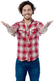 Young casual man welcoming you Royalty Free Stock Photo