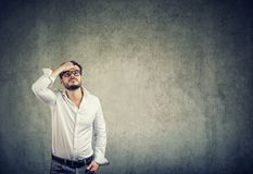 Young man in white shirt and glasses having problems and looking up in challenge on gray wall background royalty free stock image