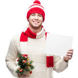 Young casual man in winter hat hoding christmas tree and sign Royalty Free Stock Photo