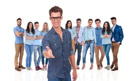 Casual young man welcomes you to his team. Young casual men with eyeglasses welcomes you with a handshake in his group of people royalty free stock image
