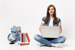 Young casual pretty smiling woman student holding using laptop pc computer sitting near globe, backpack, school books. Isolated on white background. Education royalty free stock photos