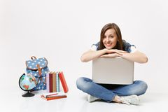 Young casual pretty smiling woman student leaning on laptop pc computer and sitting near globe backpack, school books. Isolated on white background. Education stock image