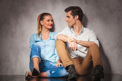 Young casual seated couple laughing at each other Stock Photos